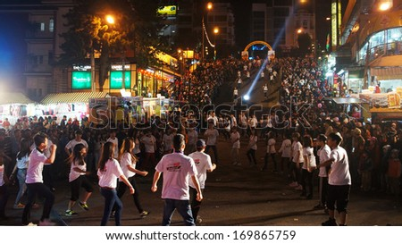 DA LAT, VIET NAM- DEC 29- Lifestyle of young people, they dance with team at outdoor night to celebrate New Year at Flower festival, large audience cheer under limelight, Dalat, Vietnam, Dec 29, 2013