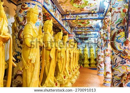 DA LAT, VIETNAM - MARCH 20, 2015: Golden Buddha statues along the wall in the interior of the Linh Phuoc Pagoda in Da Lat city (Dalat), Vietnam. Da Lat is a popular tourist destination of Asia.