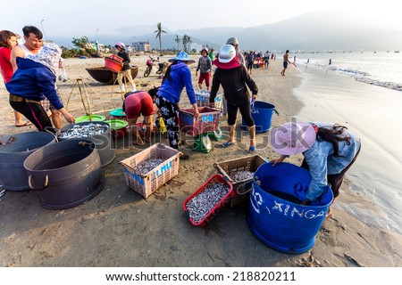 DA NANG CITY, VIETNAM - APRIL 30, 2014 - People busy selling and buying sea food on the beach just after the vessels\' arrival. May 30 is the Victory Day in Vietnam.
