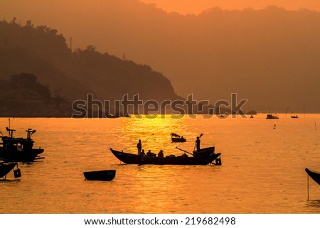 DA NANG CITY, VIETNAM - APRIL 30, 2014 - Unidentified fishermen  fishing at sunrise on the sea. May 30 is the Victory Day in Vietnam and many tourists come to this place for entertainment.