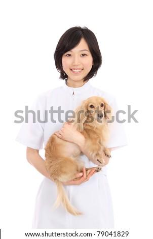 Dachshund and Asian women in white coats - stock photo