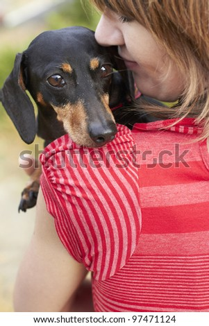 Dachshund dog looking over shoulder while owner gives a loving hug