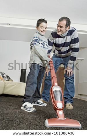 Dad and boy using a vacuum cleaner at home.