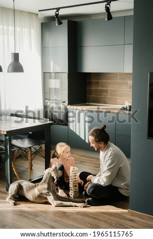 Dad and daughter are playing a board game in the kitchen, sitting on the floor. A dog is lying nearby. Scandinavian and high-tech style in the interior. Family leisure Foto stock ©