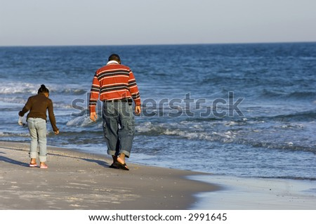 Dad and daughter looking for clams on the beach of Gulf of Mexico