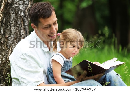 Dad and daughter reading the Bible