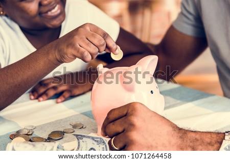 Dad and daughter saving money to piggy bank