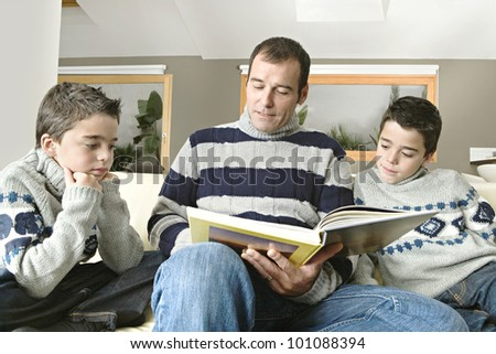 Dad and identical twin sons reading a book at home together.