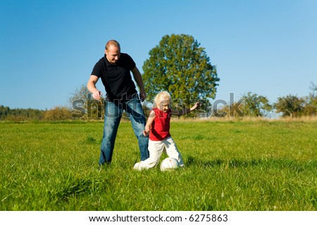 Dad and little daughter playing soccer on a green meadow under a perfect blue sky