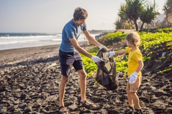Dad and son are cleaning up the beach. Natural education of children