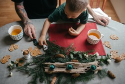 Dad and son are playing cars. The family is sitting at the dinner table. Time with a child. Hands  father with a tattoo. New Year's decor. Gingerbread cookies, New Year's candles. Christmas Eve. Chris