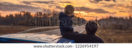 Dad and son are resting on the side of the road on a road trip. Road trip with children concept BANNER, LONG FORMAT