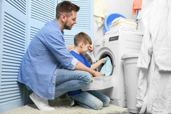Dad and son doing laundry at home