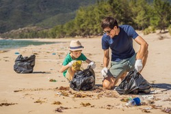 Dad and son in gloves cleaning up the beach pick up plastic bags that pollute sea. Natural education of children. Problem of spilled rubbish trash garbage on the beach sand caused by man-made