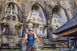 Dad and son on background of Gunung Kawi. Ancient carved in the stone temple with royal tombs. Bali, Indonesia. Traveling with children concept