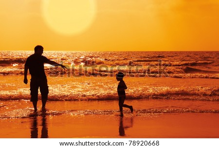 Dad and son on the beach at at sunset