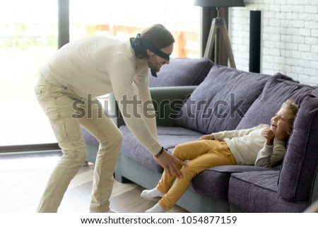 Dad and son playing hide and seek game at home, blindfolded father trying to catch excited happy child boy hiding on couch, parent and kid having fun laughing spending time together in living room