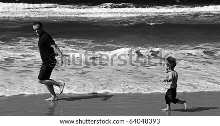 Dad and son playing on the sea. Autumn sea, strong waves, sharp colors. Black and white photo