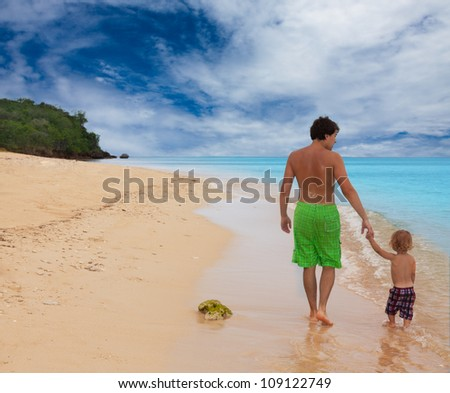 Dad and son walking on the seashore and holding hands