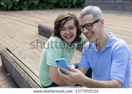 Dad and teen son are holding cell phone and looking at screen. Father laughing in sunny day. Concept of family, different generations, bonding.