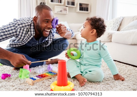 Dad and toddler son having fun playing at home, close up