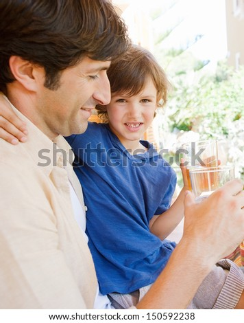 Dad and young son sitting together at a table in a home porch garden outdoors drinking water and enjoying a sunny day while on vacation.