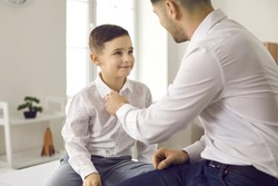 Dad as a best friend and mentor. Loving father helps his cute little son to fasten a button on his shirt. Boy wants to look like his handsome father who wears jeans and a shirt. Stylish family.