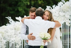 Dad congratulates the brides with a marriage and hugs. man welcomes. Happy bride and groom. On background of arch on nature in courtyard of house. Wedding ceremony. Close up.