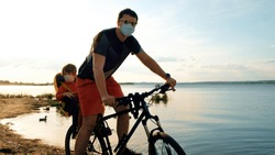 Dad driving his baby boy in protective masks on a weekend excursion with bikes on a summer day in beautiful landscape, for safety and protection they are sitting in a bike trailer