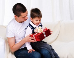 Dad gives his son a gift in red box