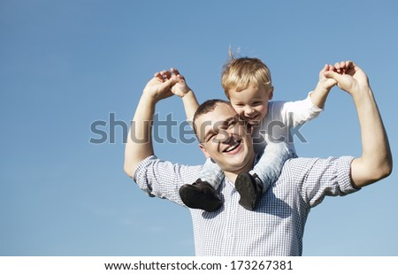 Dad giving his young son a piggy back ride as they both laugh with pleasure and enjoyment, low angle against a clear blue summer sky with copyspace