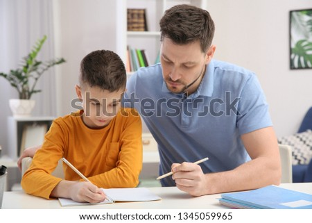 Dad helping his son with homework in room