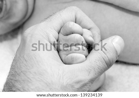 Dad holding little baby fist