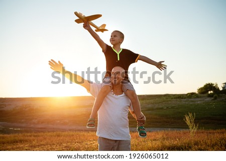 Dad holds his son around his neck at sunset in the summer they launch a plane against the background of the sky