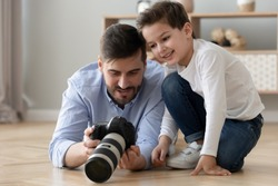 Dad holds photo camera explains teaches his little son how take photo create make art spend time together on warm floor, amateur or professional photographer share knowledge education of child concept