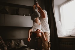 Dad holds the baby in the air by the legs, funny home photos. Authentic lifestyle and brown tinting