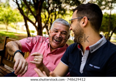 Dad interacting with his new digital watch, son happy for that