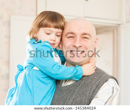 Dad is holding his daughter in his arms