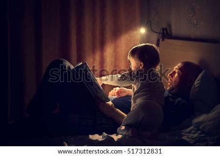 Dad is reading a bedtime story to his little son. Night lamp is shine beautifully. Image with selective focus and toning