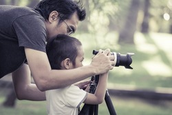 Dad is teaching photography to his son with vintage color tone