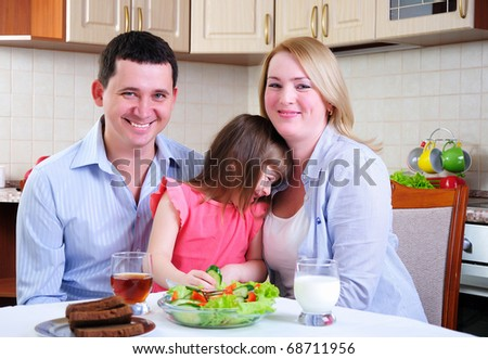 Dad, Mom and their little daughter lunching together in his kitchen.