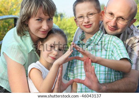 dad, mom, son and daughter is using their hands to represent home. focus on son's face.