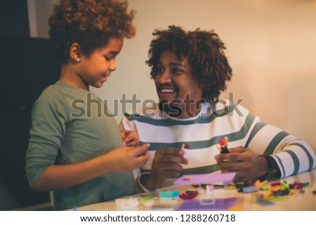 Dad most likes to play with you. African American father and daughter playing with cubes.
