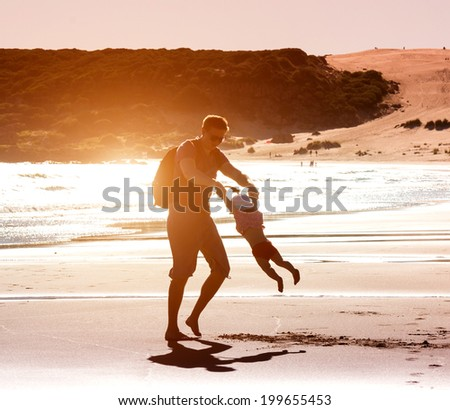 Dad playing with baby daughter on the beach at sunset