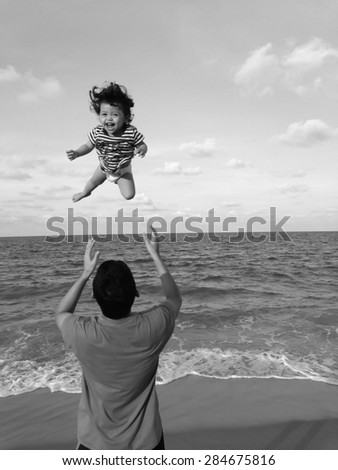 DAD PLAYING WITH CHILD ON BEACH (BLACK AND WHITE)