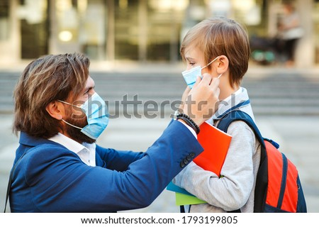 Dad putting on a protective mask on his son's face outdoors. Schoolboy is ready go to school. Cute boy with backpack. Back to school concept. Medical mask to prevent coronavirus. Coronavirus pandemic