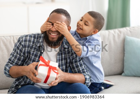 Dad's Birthday. Little Son Congratulating Black Father Giving Wrapped Gift To Him, Covering Eyes Sitting On Couch At Home. Family Holiday Celebration, Surprise Present For Daddy's B-Day