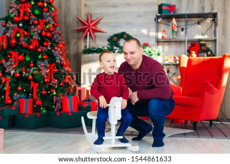 Dad sits next to his son. boy sitting on rocking horse. cozy room with Christmas tree and armchair. play.  #1544861633