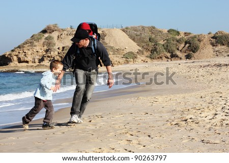 Dad, son and daughter during a walk along the sea running from the waves