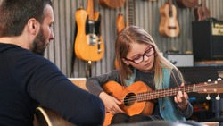 Dad teaching guitar and ukulele to his daughter.Little girl learning guitar at home.Close up.Ukulele class at home. Child learning guitar from her father